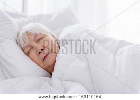 Self-possessed granny sleeping in white soft bed in apartment of clinic