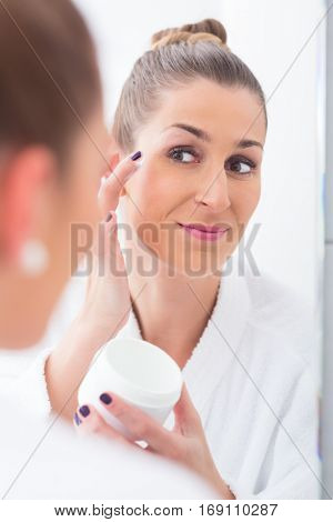 Woman with eye mask and in bathrobe removing her makeup before sleeping