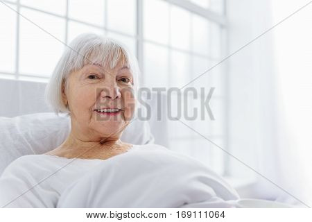 Smiling old woman staying in soft white bed near big window in polyclinic