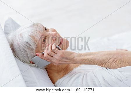 Cheerful old woman telling by mobile while staying in soft bed