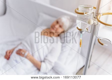 Cool old woman is on glass-dropper while lying on soft white bed in hospital