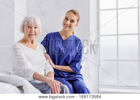 Your health is good. Outgoing attractive young physician describing level of health of grandmother while sitting near female pensioner in room of clinic
