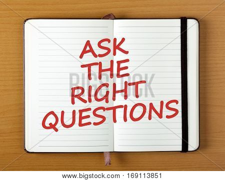 The words Ask The Right Questions in red ink on an open notebook as a reminder to prepare for an interview or obtain the answers to a problem