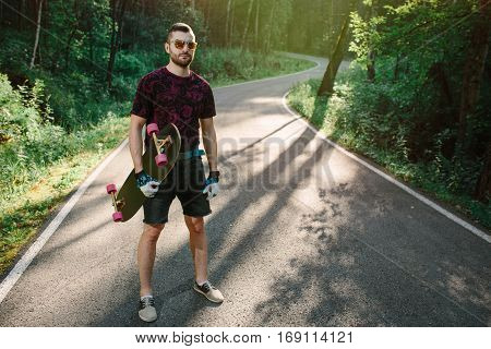 A Skater With Longboard Is Standing On Road In Nature Background