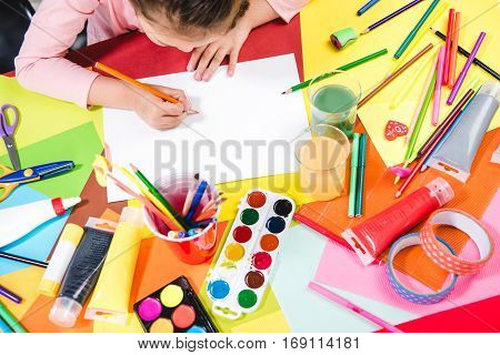 Overhead view of schoolchild drawing picture at table with school supplies