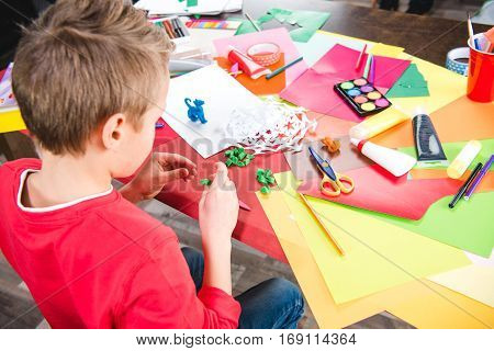 Schoolchild sitting at table and making toy from plasticine