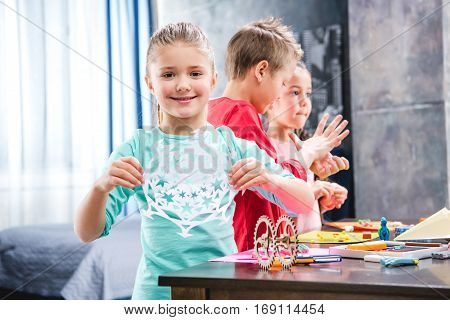 Kid cutting snowflake from paper schoolchildren playing with colorful plasticine