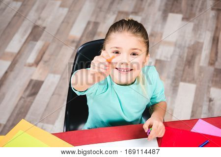Smiling schoolchild pointing at camera with pencil