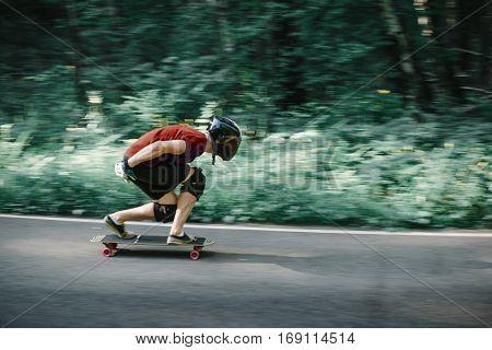 Skater Boy In Helmet On Longboard Going On Road In Beauty Nature
