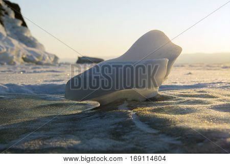 Siberia, Lake Baikal. Small piece milk color of ice in the rising sun.