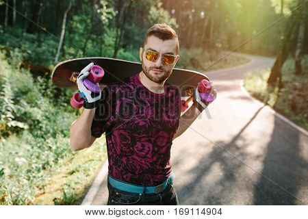 Cool skater guy holding a longboard on road in nature park