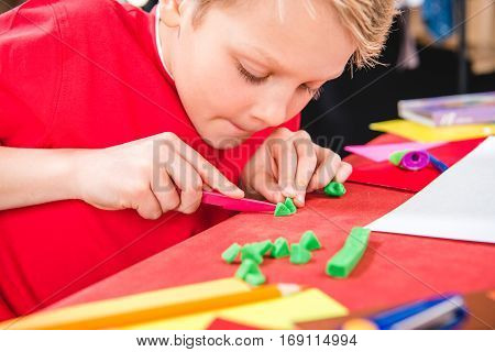 Concentrated schoolchild cutting green plasticine in school