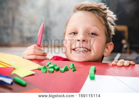 Smiling schoolchild cutting green plasticine and looking at camera