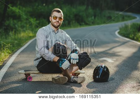 A skater with a board is siting on road in nature background. Young male wearing t-shirt and shorts