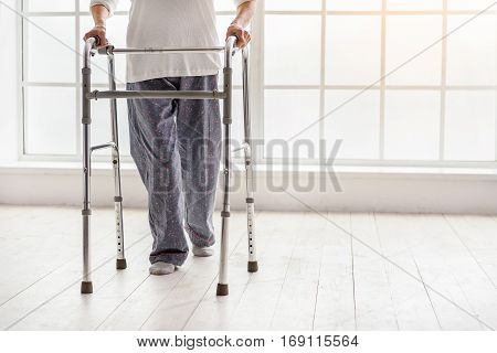 Retiree keeping walking frame in her hand while going in apartment of clinic