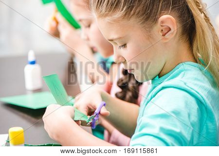 Schoolchildren making applique with paper and scissors in school