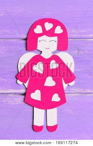 Angel doll with hearts of cardboard. Nice angel isolated on lilac wooden background with copy space for text. Valentine's day symbol. Top view. Closeup