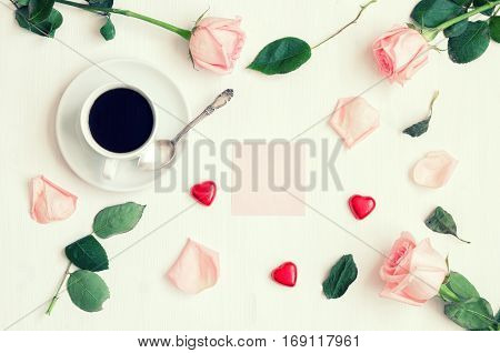 Romantic flat lay still life - cup of coffee peach roses pink sheet of note heart shaped candies in retro tones. Romantic background. Still life with romantic mood