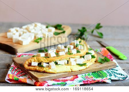 Stuffed omelet on a wooden board and a textile napkin. Omelet stuffed with tofu and garnished with parsley. Cut tofu on a wooden board, knife, parsley sprigs on a vintage table. Closeup