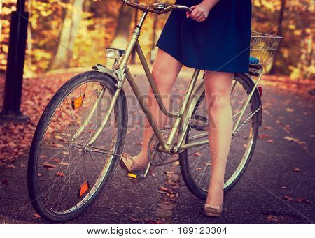 Nature outdoors activities concept. Lady in blue dress on the bike. Girl is on the footpath with her bicycle.