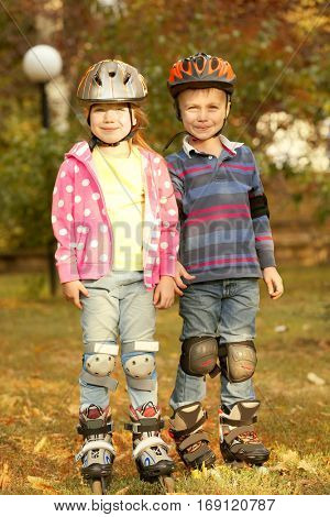 Cute little girl and boy on roller skates in park