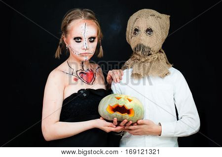 Boy and Girl with Halloween Makeup holding Pumpkin