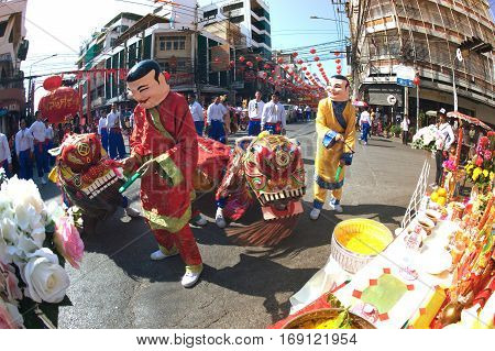 NAKHONSAWAN ,THAILAND - JANUARY 31,2017 : Unidentified people dance with Chinese Lion of Gods doing ritual at worship altar table during the Chinese New Year celebrations in Nakhonsawan Province , Middle of Thailand.