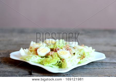Vegetable salad with tuna and quail eggs on a plate and vintage wooden table. Salad with chinese cabbage, canned tuna and hard-boiled quail eggs. Closeup