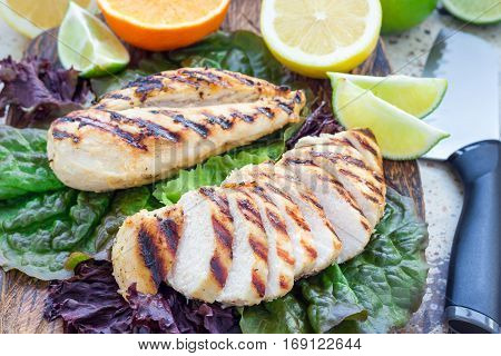 Grilled chicken breast in citrus marinade on salad leaves and wooden cutting board horizontal