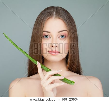 Young Woman Spa Model and Green Aloe Leaf. Spa Beauty and Skincare Concept