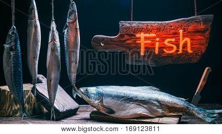 Fresh salmon and hanging mackerel in vintage fish market under wood sign