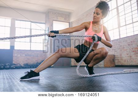 Shot of young african woman doing exercises with rope at a gym. Fitness female pulling rope at gym.