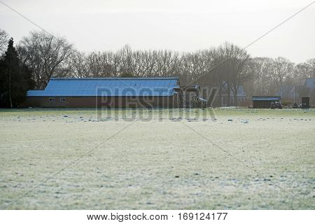 Farm cattle shed with frozen roof in rural winter landscape.