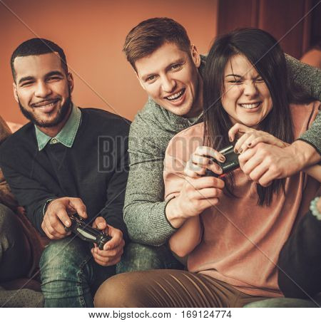 Group of multi ethnic friends having fun playing on game console in home interior.