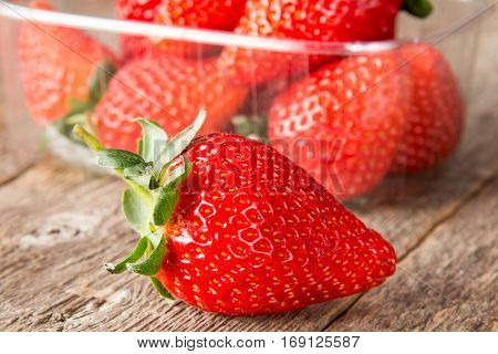 Red strawberry with box full of strawberries in a background
