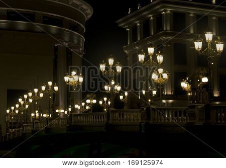 Golden lamppost lights, on bridge, lighting the path to the baroque building