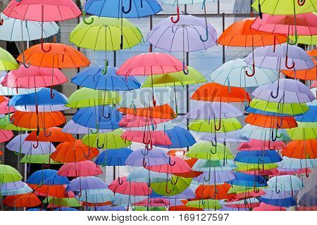 Bright colorful umbrellas as street decoration hanging up in the open air