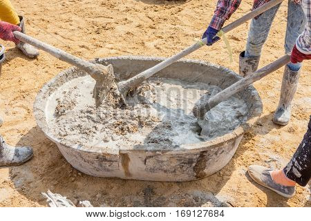 Concrete workers mixing the cement and sand in grunge steel salver building construction site.