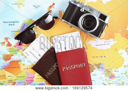 Adventure concept. Camera, sunglasses, passports with tickets on map