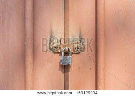 Closeup the metal padlock fasten on old rusty metal entrance doors security and private zone.