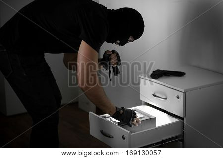 Thief entering password on safe
