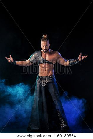 Young and muscular man performing a theatrical pose on a stage. Very sexy man in stage costume