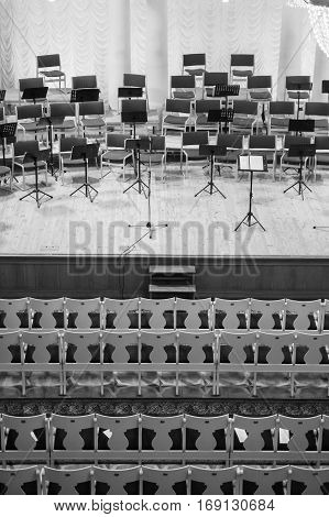 Empty auditorium and the stage before the concert. On the stage music stands with notes. Black and white photo
