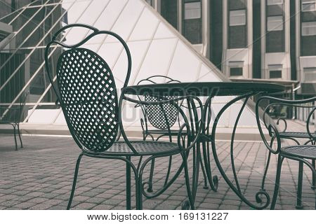 Vintage metal chairs and table are in the yard against the backdrop of modern buildings of glass