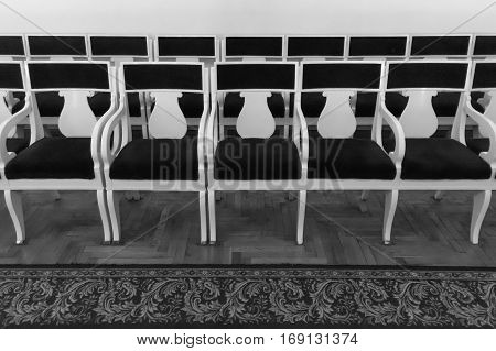 Rows of old chairs in the auditorium. Black and white photo