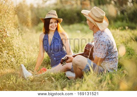 Happy couple having fun together and enjoying together outdoors sitting on grass on pier of lake. Boyfriend and girlfriend playing on guitar at sunset. Wife and husband wearing hats