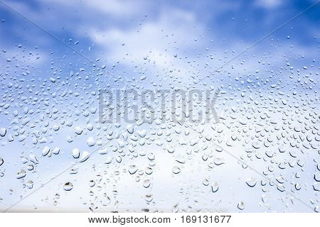 Rain drops on the glass in the background blurred blue cloudy sky. After raining concept