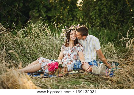 Portrait of couple of boyfriend and girlfriend sitting among grass in meadow kissing embracing and enjoying each other. Wife in dress and wreath of flowers husband in white shirt. Picnic outdoor.