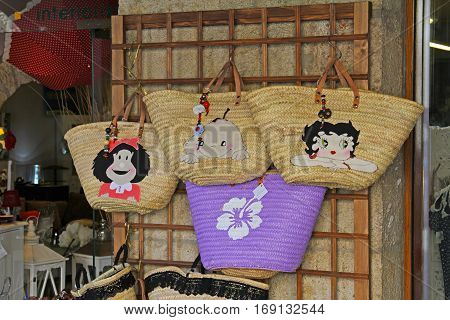 Besalu Spain - September 09 2014: Straw bags bags for sale in street shop in Besalu