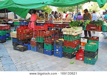 Besalu Spain - September 09 2014: Sale of fruit and vegetables in street of Besalu in Spain. Fruit and vegetables in plastic and wooden boxes at farm market.
